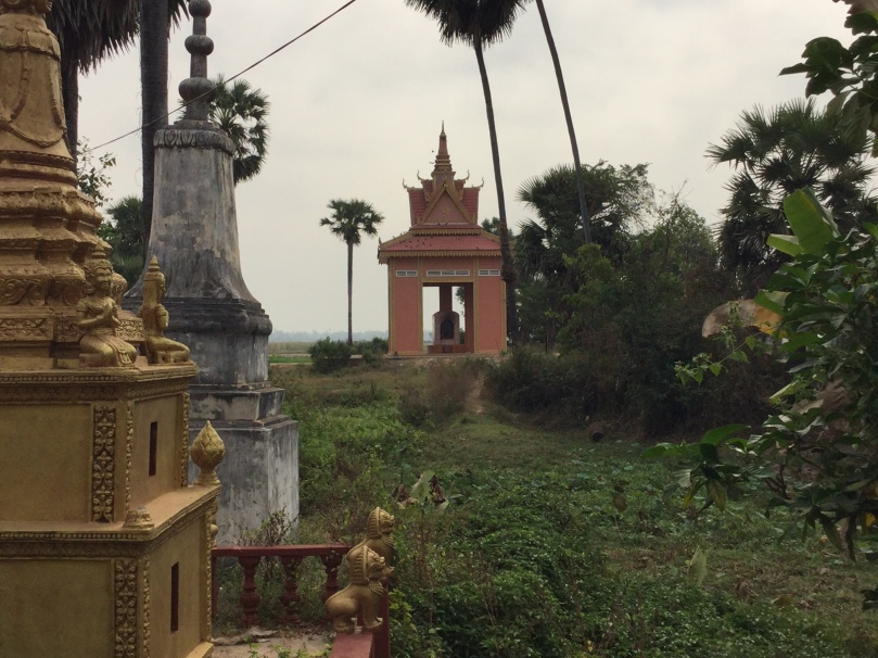 A crematorium sits in the distance behind a temple in Cambodia.